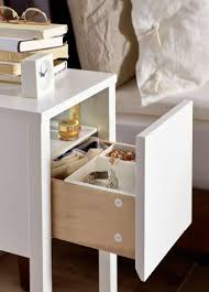 Close-up of small IKEA bedside table, drawer open to reveal inside storage x