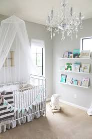 crystal chandelier lighting and baby girl room also rectangular crib bed also floating wall shelves with lip and animal rocking chair