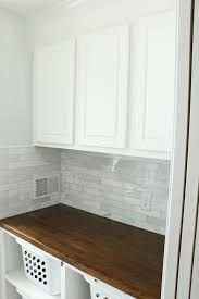 chic laundry room with white stock cabinets with wood countertop and marble subway tile backsplash