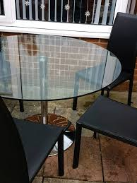 large round glass table and 5 chairs