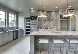 kitchen with light gray cabinets white granite countertops and drum pendant lights