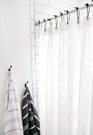 white shower curtain black hooks minimal bathroom