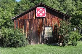 What Are Barn Quilts? A Look at Barn Quilts & Their History & Barn in Trees with Red Barn Quilt Adamdwight.com
