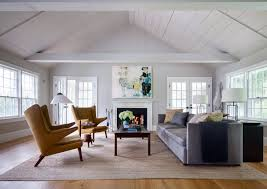 remodeled colonial house with modern decor using tufted armchairs and  modern wall arts also white paint