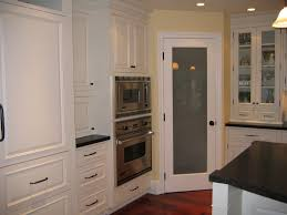 white kitchen design with tall corner kitchen pantry cabinet with frosted glass door