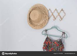 close up of hat and dress hanging against white wall photo by wavebreakmedia