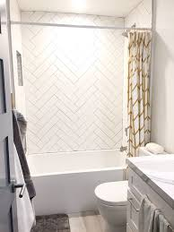 grouting wall tile shower. guest shower. herringbone white subway tile gray grout. gold accent grouting wall shower h