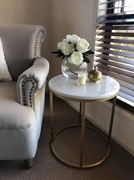 she sprayed painted the marble side table in gold perfect for adding a touch of luxe without breaking the budget