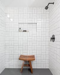 black and white shower tiles with teak shower stool