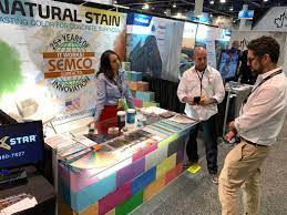 Sona Shah, national project integrator at Semco Modern Seamless Surface,  left, and Adam Nitte talk to Robert Polo of Valencia, California in their  booth at the World of Concrete trade show at