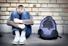 what are the adult health consequences of childhood bullying  teenager hugging his knees