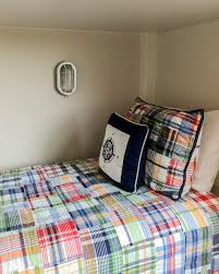 quarters found on sailing vessels allowing it to take advantage of an otherwise tight space in a truly nautical fashion madras plaid bedding in bright