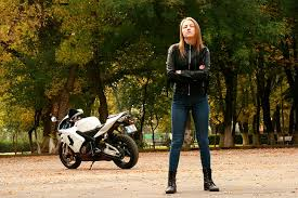 woman wearing black leather zip up jacket with motorcycle
