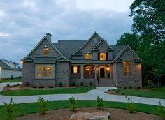 This home features a brick exterior   arch topped windows    Two story brick home   European style exterior  Evening view of The Rochelle