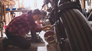 woman working on motorcycle in a garage