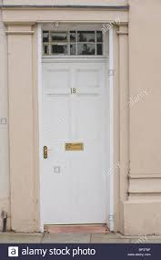 white painted wooden paneled front door no 18 with brass handle letterbox and fanlight of period town house in uk