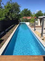 Above ground lap pool with remco remote controlled pool cover stored under  wooden deck.