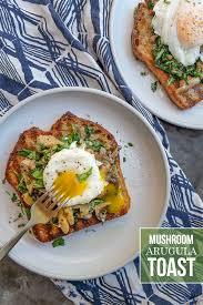 creamy mushroom arugula toast with poached eggs find the recipe on shutterbean