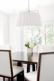 white scalloped drum pendant light with brown rectangular dining table