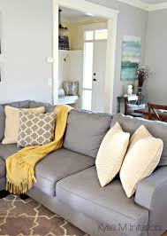 how to make a gray paint colour feel warm shown in living room with revere pewter gray sectional and yellow and blue accents and home decor by kylie m