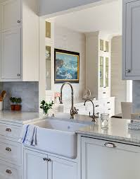 a farmhouse sink and gooseneck faucet stands under a kitchen pass through which overlooks the formal dining room