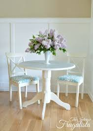 round pedestal table makeover with painted doily top and two cross back chairs