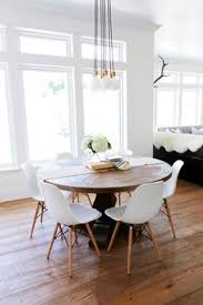 dining room rustic round wood table surrounded by white eames dining chairs creates an interesting mix in this transitional eat in kitchen