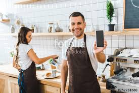 Handsome Cashier Showing Smartphone With Blank Screen Wile