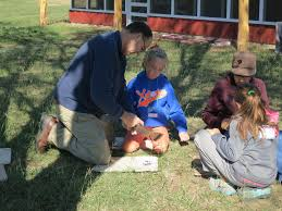 Albany ISD Superintendent Shane Fields helps students create talking sticks  during a Native American activity - Kids On the Land