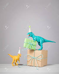 stock photo two dinosaurs with birthday hats and gifts on a light grey background