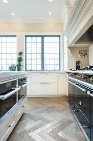 natural light comes in from a blue framed window hitting herringbone wood floors separating a white kitchen island fitted with honed white marble