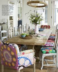 country living march 2018 vine rustic eclectic artsy style dining room suzani fabric covers on silver painted wood chairs by redford house and