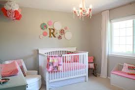 white baby room design with white cradler and bedding decorated with flowers and cute pink crystal chandelier