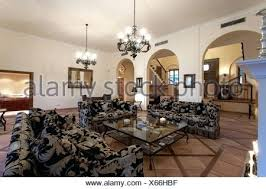 large patterned sofas and glass coffee table in modern living room with metal chandeliers spanish meaning