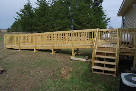 closer view of start of wheelchair ramp including step access to the home