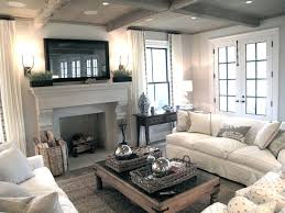jane green figless manor chic cozy living room with framed tv over stone fireplace herringbone firebox rustic wood coffered ceiling french doors chic family room decorating