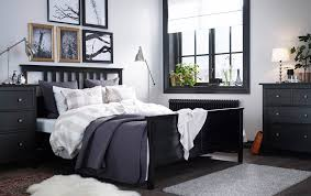 a large bedroom with a black brown bed with bed textiles in beigewhite big brown ikea hemnes linen