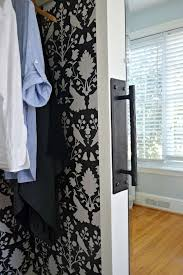 mirrored closet door with iron handle and clothes hanging in it