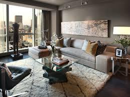 The dark wood floors of this modestly sized but comfortable living room are  covered by a