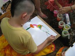 gabriel started by painting the orange flower and then moved onto the hummingbird starting with