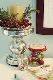 Christmas vignette with mercury glass, vintage jar of small ornaments, and  berries with candle