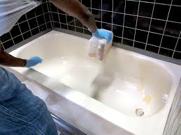 tech applying chemical stripper to ling tub