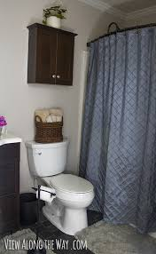 bathroom with blue gray shower curtain and dark wood accents