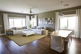 white taupe living room dining room combo with white slip covered sofas white tufted ottoman sisal rug white ds taupe walls paint color