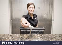 female hotel front desk clerk handing keycard