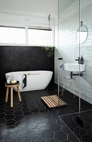 large scale black hex tiles cover the floor and go up the wall and contrast the