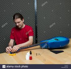 Guitar Technician Guitar Technician Replacing The Strings Of An Electro Acoustic