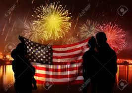 Family With American Flag And Fireworks In Sky Holiday Celebration