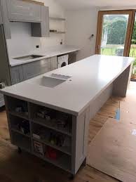 corian designer white island and hob worktop with cove upstand splashback and 969 967 1 5 bowl sinks with drainer grooves installed in caerleon newport