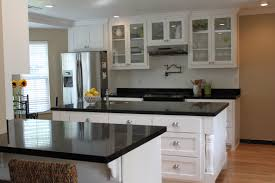 kitchen white wooden kitchen cabinet with glass door plus black counter top and drawers placed